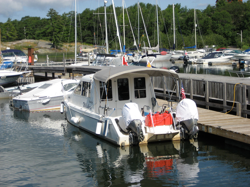 Photo: Twin engine catamaran with missing gear cases on both outboard motors Killbear Marina, Parry Sound region, Ontario.