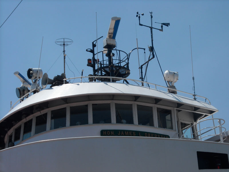 Photo: Close-up of antennas, RADAR, spotlights, horn, and searchlights on superstructure of HON. JAMES L. OBERSTAR