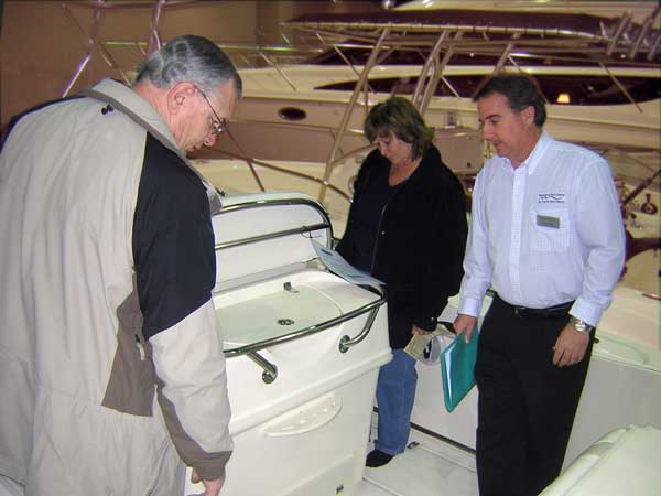 Photo: Boston Whaler Sales Manager Dennis Tilden shows the 270 OUTRAGE to some prospective buyers at the Detroit Boat Show, February 19,2006